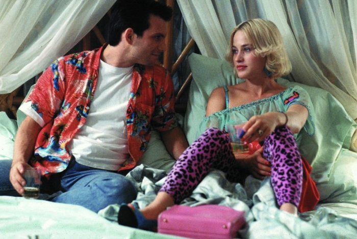Photo de Christian Slater et Patricia Arquette dans le film True Romance de Tony Scott. Assis dans un lit, les deux acteurs échangent un regard et sourient.