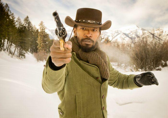 Photo de Jamie Foxx dans le film Django Unchained de Quentin Tarantino. Dans des montagnes enneigées, Jamie Foxx est face à l'objectif et brandit son revolver.