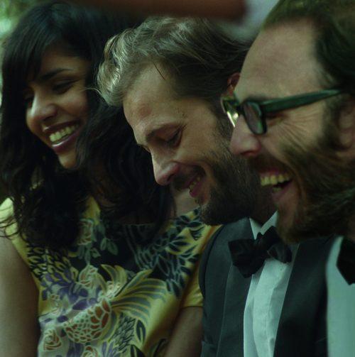 Photo du film Mariage à Mendoza sur laquelle les personnages principaux rient de bon coeur et côte à côte lors d'un mariage.