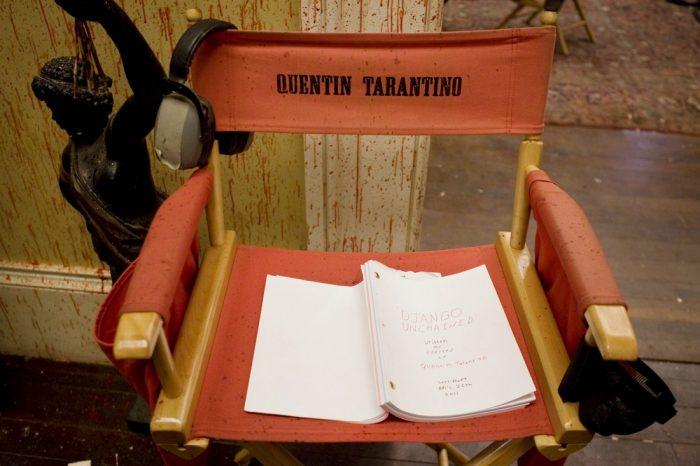 Photo de plateau du film Django Unchained sur laquelle la chaise de Tarantino est installée devant un décor ensanglanté. Le scénario est posé sur la chaise.