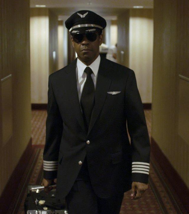 Photo de Denzel Washington dans le film Flight de Robert Zemeckis. L'acteur avance vers l'objectif dans un couloir d'hôtel en tenue de pilote d'avion.