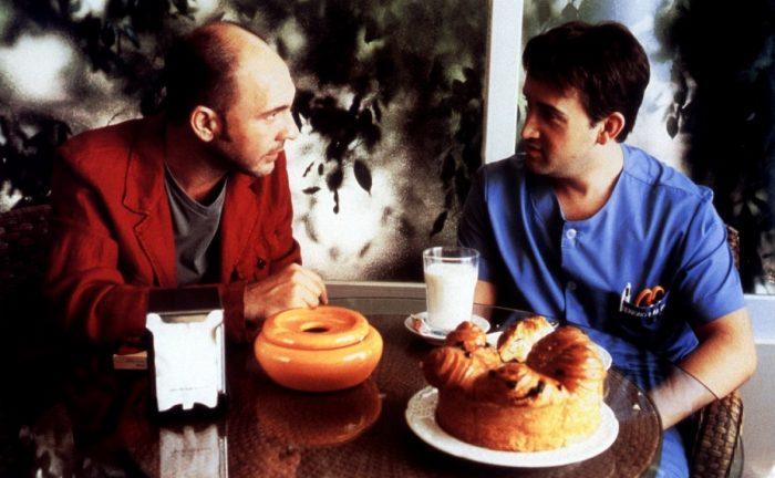 Photo du film Parle avec elle de Pedro Almodovar sur laquelle Dario Grandinetti et Javier Camara discutent autour d'un petit déjeuner.