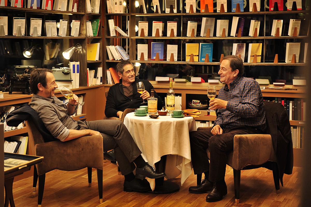 Photo de Jean-Hugues Anglade, Gérard Lanvin et Wladimir Yordanoff dans le film Amitiés Sincères. A table, les trois amis boivent un verre de vin et rient ensemble dans la librairie de Yordanoff.