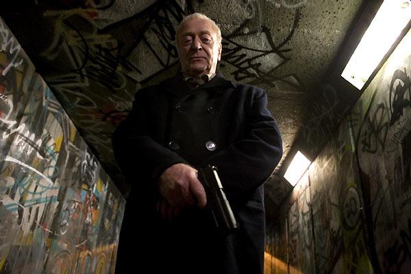 Photo de Michael Caine dans le film Harry Brown. L'acteur est pris en contre-plongée dans un tunnel piéton de la banlieue londonienne. Il est armé et semble contempler une victime.