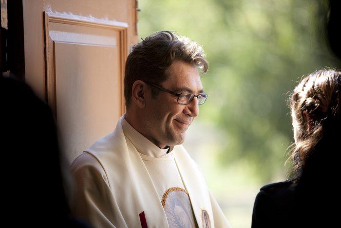 Photo de Javier Bardem dans le film A la merveille de Terrence Malick. Le prêtre est à l'entrée d'une église et sourit à une personne.