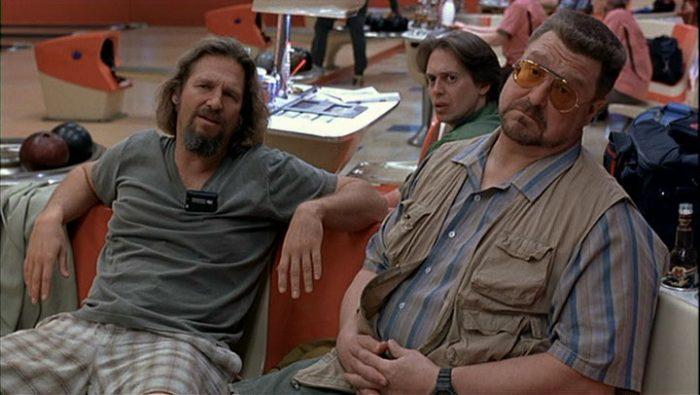 Photo de Jeff Bridges, Steve Buscemi et John Goodman dans le film The Big Lebowski des frères Coen. Les trois acteurs regardent le personnage de Jesus interprété par John Turturro assis sur leur banc de bowling. Ils paraissent effarés.