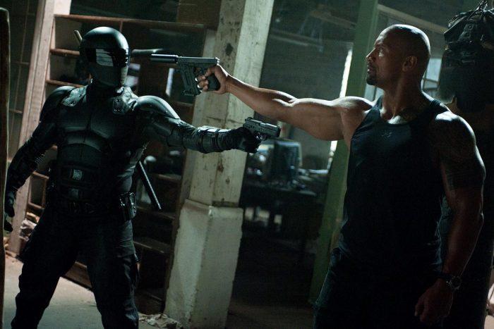 Photo de The Rock dans le film G.I. Joe. L'acteur pointe son arme vers un ennemi entièrement vêtu de noir, qui pointe lui aussi une arme sur son adversaire.