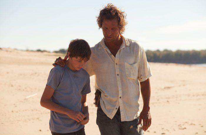 Photo de Tye Sheridan et Matthew McConaughey dans le film Mud de Jeff Nichols. Les deux acteurs marchent sur une plage et discutent. McConaughey pose sa main sur l'épaule de Sheridan.
