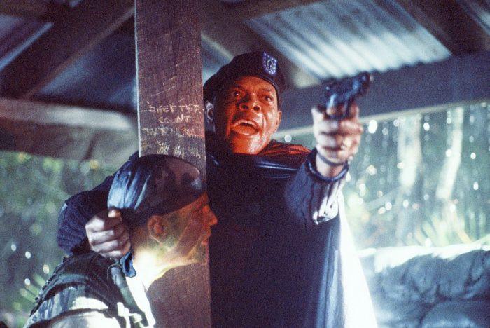 Photo de Samuel L. Jackson dans le film Basic de John McTiernan. Dans la jungler, l'acteur est sous un refuge inondé, tient un soldat par la nuque et pointe son arme vers un autre homme en hurlant.
