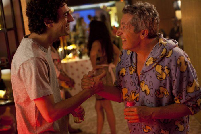 Photo de Max Boublil et Alain Chabat dans le film Les Gamins. Pendant une soirée, les deux acteurs rient ensemble et se serrent la main amicalement.