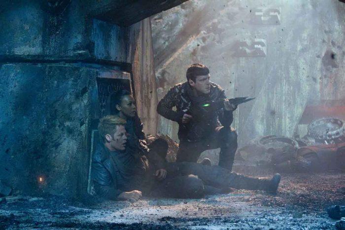 Photo de Chris Pine, Zoé Saldana et Zachary Quinto dans Star Trek : Into Darkness. Dans une grotte, Pine et Saldana sont au sol alors que Quinto semble les protéger avec une arme.