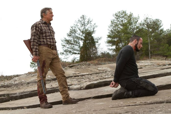 Photo de Robert De Niro et John Travolta dans le film Killing Season. Dans la nature, Travolta est à genoux et a les mains ligotées derrière son dos. Derrière lui se tient Robert De Niro qui tient un fusil.