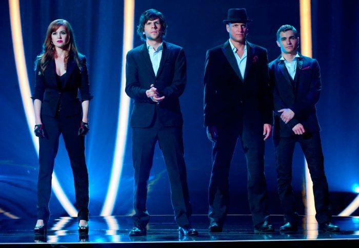 Photo d'Isla Fisher, Jesse Eisenberg, Woody Harrelson et Dave Franco dans le film Insaisissables. Ls quatre magiciens sont face à un public et s'apprêtent à faire un tour.