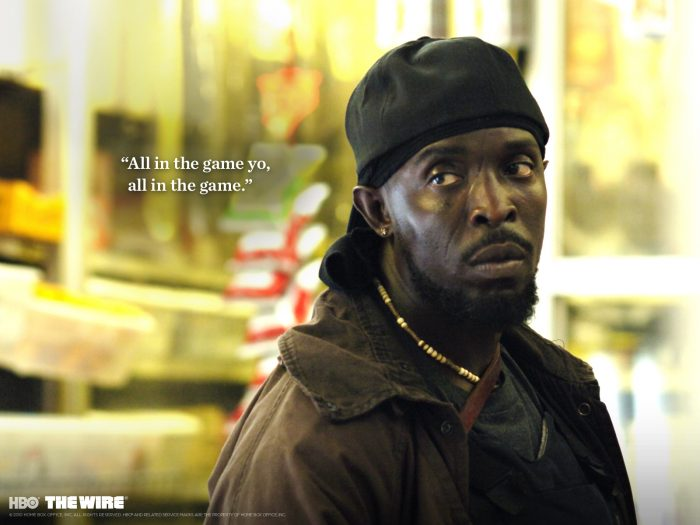 "Photo de Michael Kenneth Williams dans The Wire. Omar Little semble regarder un autre personnage. Sa phrase ""All in the game yo, all in the game"" est inscrite à côté de son visage comme une citation."