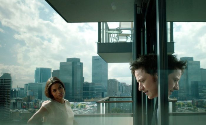 Photo de Rosario Dawson et James McAvoy dans le film Trance de Danny Boyle. Sur un balcon, James McAvoy parle à Rosario Dawson qui le regarde tendrement.