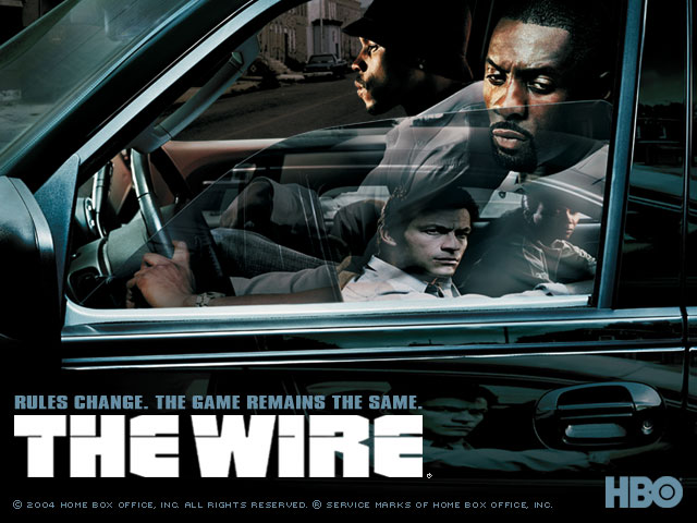 Bannière de la saison 3 de The Wire. Nous y voyons Stringer Bell et Avon Barksdale passer face à une voiture occupée par McNulty et Greggs.