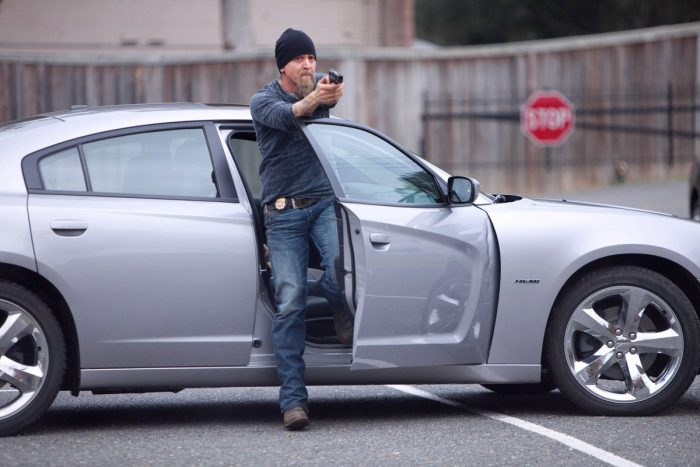 Photo de Barry Pepper dans le film Infiltré. L'acteur est un policier qui sort de sa voiture en travers de la route et pointe son arme vers un suspect.