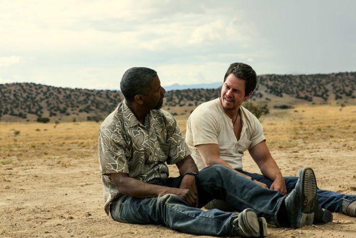 Photo de Denzel Washington et Mark Wahlberg dans le film Top Cops. Les deux acteurs sont assis côte à côte dans le désert, semblent épuiser et discutent.