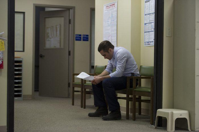 Photo de Jake Gyllenhaal dans le film Prisoners de Denis Villeneuve. L'acteur attend assis dans une grande pièce et observe une feuille qu'il tient dans ses mains.