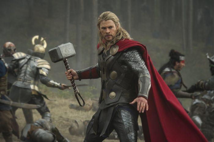 Photo de Chris Hemsworth dans le film Thor : Le Monde des ténèbres. Thor tient son marteau sur un champ de bataille, prêt à combattre.