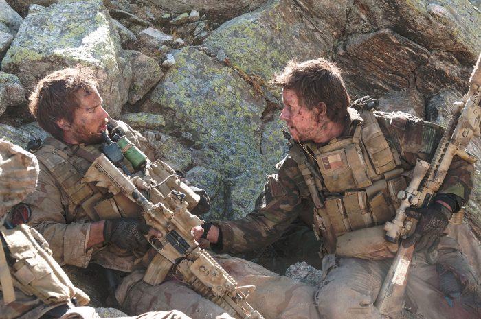 Photo de Taylor Kitsch et Mark Wahlberg dans le film Du sang et des larmes de Peter Berg. Assaillis, les deux soldats sont réfugiés derrière un rocher. Wahlberg semble donner des ordres à Kitsch.