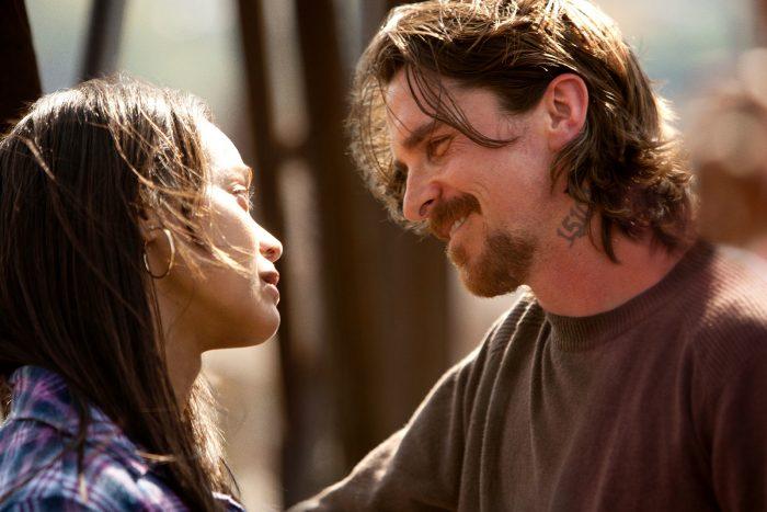 Photo de Zöe Saldana et Christian Bale dans le film Les brasiers de la colère de Scott Cooper. Dans une rue ensoleillée, les deux personnages se regardent. Bale adresse un sourire à Saldana qui semble bien plus mélancolique.