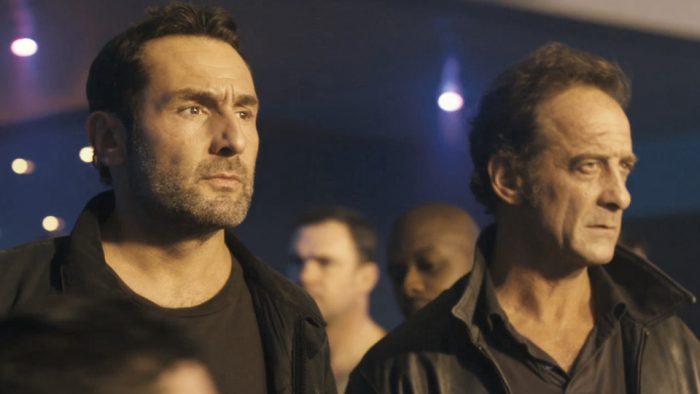 Photo de Gilles Lellouche et Vincent Lindon dans le film Mea Culpa de Fred Cavayé. Les deux acteurs sont dans une boîte de nuit et semblent chercher quelqu'un.