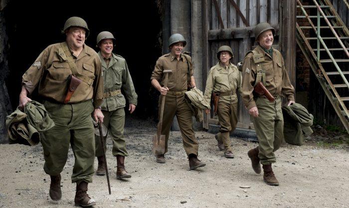 Photo du film Monuments Men de George Clooney. Nous le voyons aux côtés de Matt Damon, John Goodman, Bill Murray et Bob Balaban marcher en tenue de soldats.