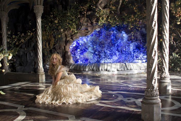 Photo de Léa Seydoux dans le film La Belle et la Bête de Christophe Gans. L'actrice est vêtue dans une robe, assise sur le sol d'une luxueuse pièce enchantée.