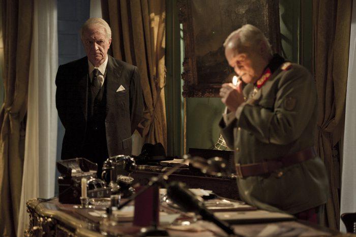 Photo d'André Dussollier et Niels Arestrup dans le film Diplomatie. Dans une chambre, Dussollier observe Arestrup en costume de soldat allemand en train d'allumer sa cigarette.