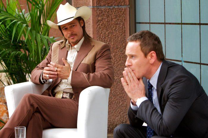 Photo de Brad Pitt et Michael Fassbender dans le film Cartel de Ridley Scott. Les deux hommes discutent assis. Pitt semble serein et alors que Fassbender paraît stressé.