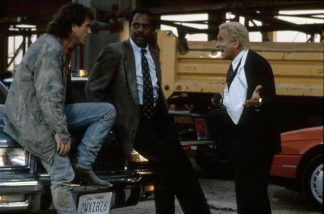 Photo de Mel Gibson, Danny Glover et Joe Pesci discutant sur un parking dans le film L'arme fatale 3 de Richard Donner. Gibson et Glover sont adossés à une voiture alors que Pesci hurle, un bras dans le plâtre.