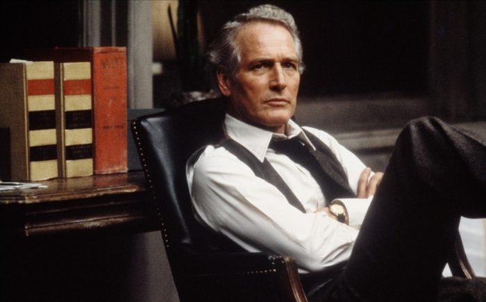 Photo de Paul Newman dans le film Le Verdict de Sidney Lumet. L'acteur est assis sur une chaise de bureau et semble écouter attentivement un autre personnage.