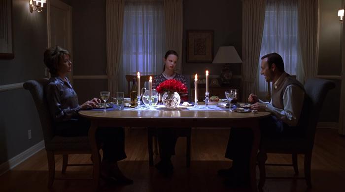 Photo d'Annette Benning, Thora Birch et Kevin Spacey dans le film American Beauty de Sam Mendes. Les trois dînent et les deux femmes semblent excédées par les paroles de Spacey.