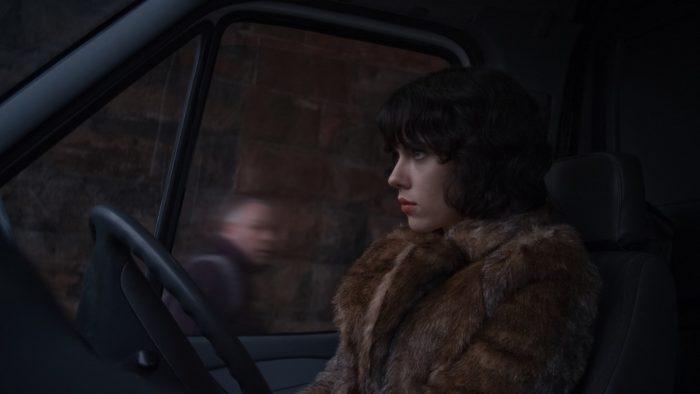 Photo de Scarlett Johansson dans le film Under The Skin. Elle est au volant d'un véhicule alors qu'un passant l'observe en marchant.