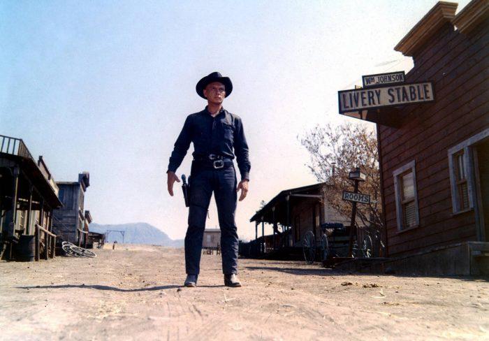 Photo de Yul Brynner dans Westworld. Vêtu de noir, le cowboy se tient prêt à dégainer dans une vieille rue déserte.