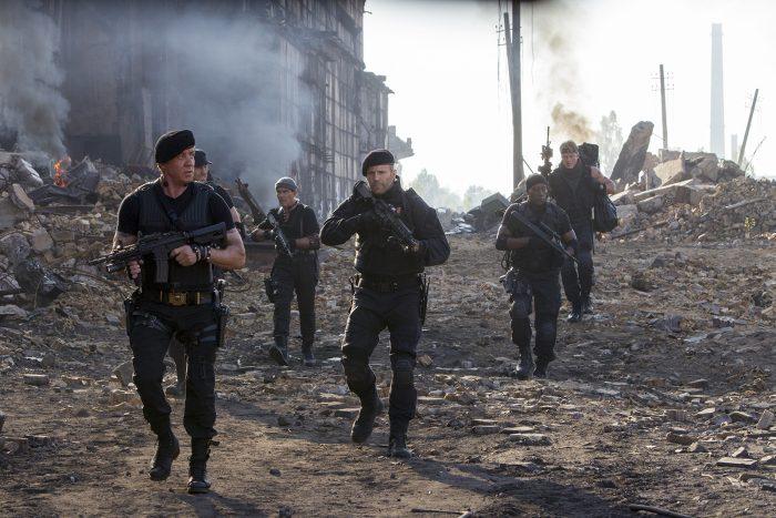 Photo de l'équipe des Expendables dans le troisième opus. Ils avancent ensemble et armés dans un paysage dévasté.