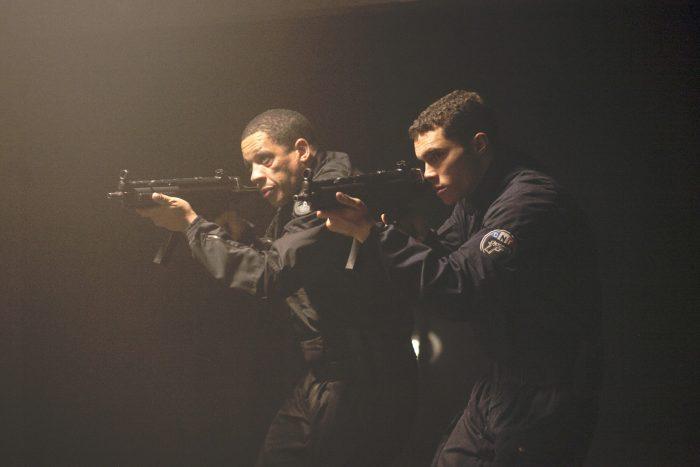 Photo de Joeystarr et Ymanol Perset dans le film Colt 45. En tenue de policier, les deux hommes avancent dans un endroit sombre en brandissant leurs armes.