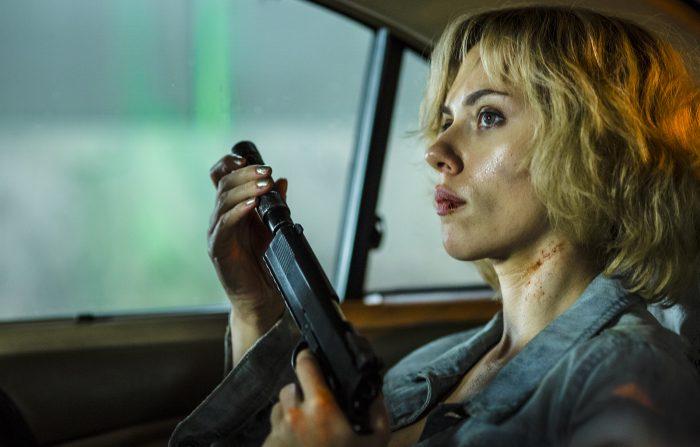 Photo de Scarlett Johansson dans le film Lucy de Luc Besson. L'actrice visse un chargeur sur une arme à l'arrière d'une voiture.