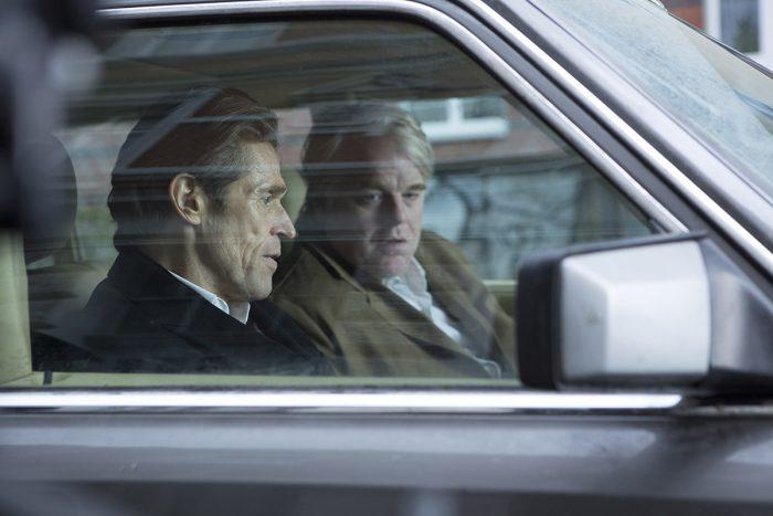 Photo de Willem Dafoe et Philip Seymour Hoffman dans le film Un homme très recherché. Les deux hommes discutent à l'intérieur d'une voiture.