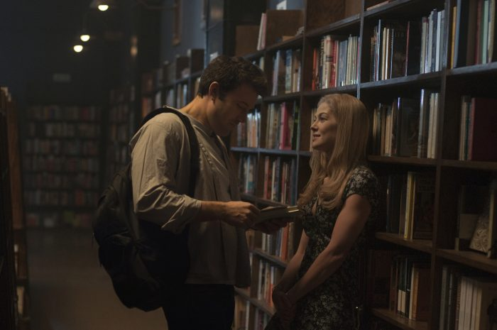 Photo de Ben Affleck et Rosamund Pike dans le film Gone Girl de David Fincher. Les deux acteurs se séduisent dans une bibliothèque.