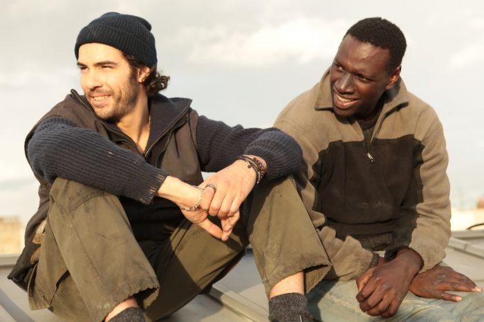 Photo de Tahar Rahim et Omar Sy dans le film Samba. Les deux acteurs sont sur un toit de Paris et rient ensemble.