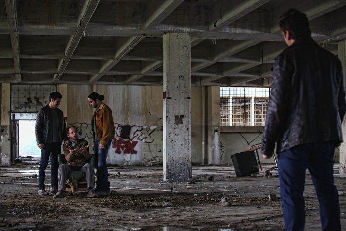 Photo tirée du film Big Bad Wolves. Nous y voyons quatre hommes dans un entrepot abandonné. L'un d'eux est ligoté et semble sous pression face aux trois autres.