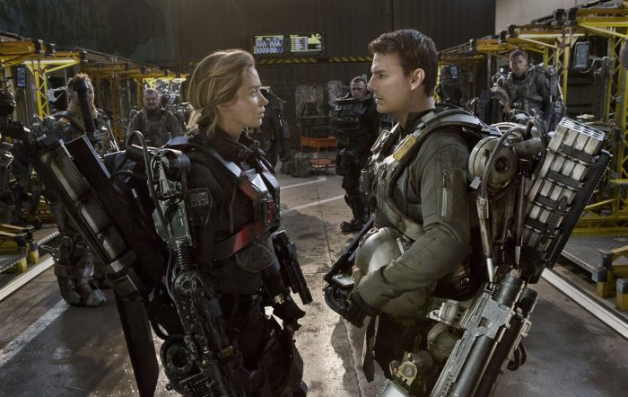 Photo d'Emily Blunt et Tom Cruise dans le film Edge of Tomorrow. Dans un entrepôt militaire, les deux personnages sont face à face dans des armures robotisées.