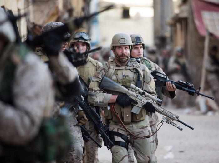 Photo de Bradley Cooper dans le film American Sniper de Clint Eastwood. Bradley Cooper marche avec d'autres soldats dans une rue irakienne.