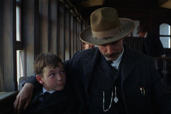 Photo de Daniel Day Lewis dans le film There Will Be Blood de Paul Thomas Anderson. L'acteur est assis dans un train avec son fils, sur lequel il a passé la main par dessus sa nuque affectueusement. Son fils semble le regarder avec admiration.