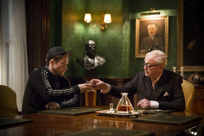 Photo de Taron Egerton et Michael Caine dans le film Kingsman de Matthew Vaughn. Les deux acteurs trinquent dans un bureau anglais.