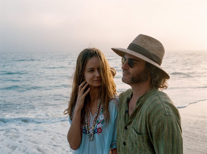Photo de Katherine Waterston et Joaquin Phoenix dans Inherent Vice de Paul Thomas Anderson. Le couple marche le long de la plage. Waterston regarde Phoenix avec un air aimant.