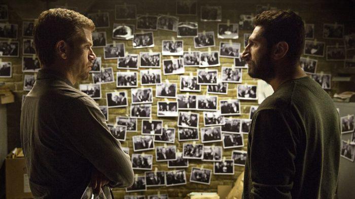 Photo du film MIséricorde. Les deux enquêteurs du Département V échangent autour de clichés accrochés au mur utiles pour l'enquête.
