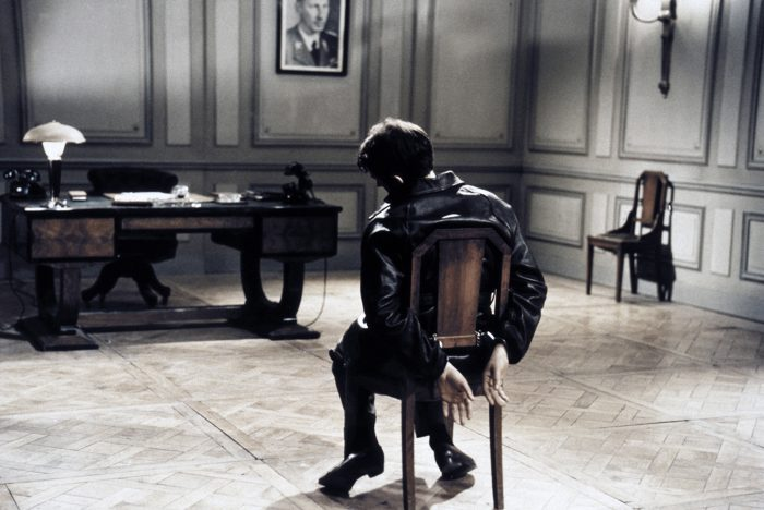 Photo de Jean Pierre Cassel dans le film L'armée des ombres de Jean-Pierre Melville. L'acteur est pris de dos, ligoté dans un bureau occupé par l'armée allemande.